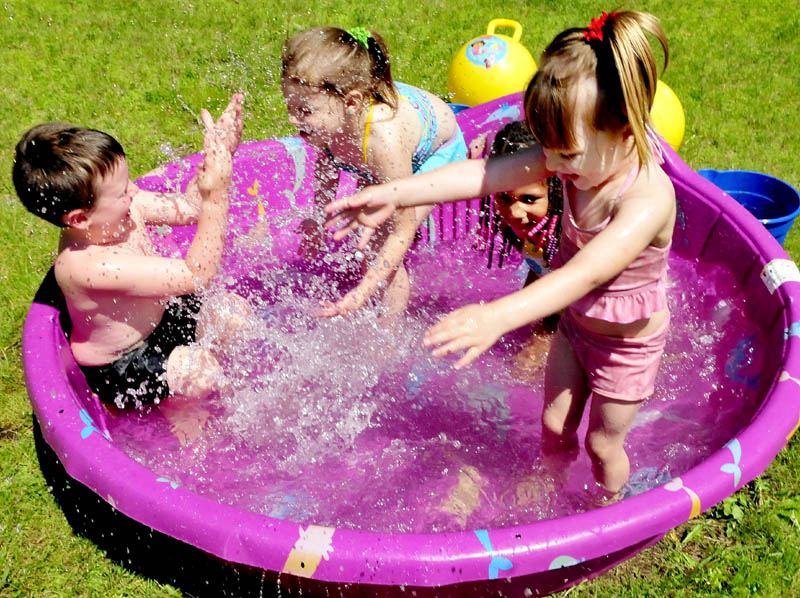 Children take a dip in a kiddie pool to cool off and have fun, in Skowhegan on Wednesday. From left are Gabe Dougherty, Kaydance Poulin, Raelynn Poulin and Rowen Rogers.