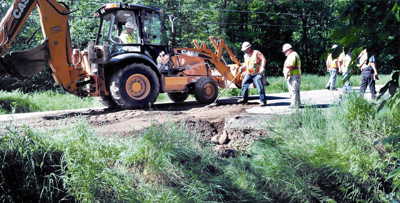 Maine Department of Transportation workers finish repairing a section of Route 148 in Industry Sunday morning. A worker said a heavy rainstorm Saturday night washed out a culvert, forcing officials to close the roadway. Road shoulders and gravel driveways in the area were also washed out.
