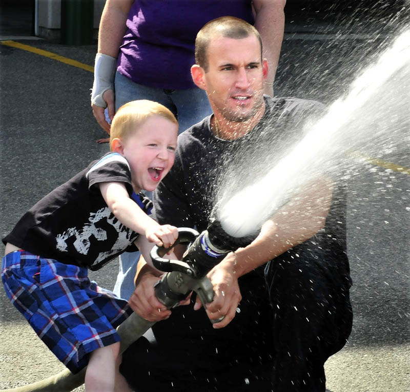 James Rackliff, a kindergarten student at the George Mitchell School, reacts with joy as he and Waterville firefighter Pablo Passalacqua turn on a water hose at Central Station on Monday. The class visited the station as part of a field day before heading to the city library.