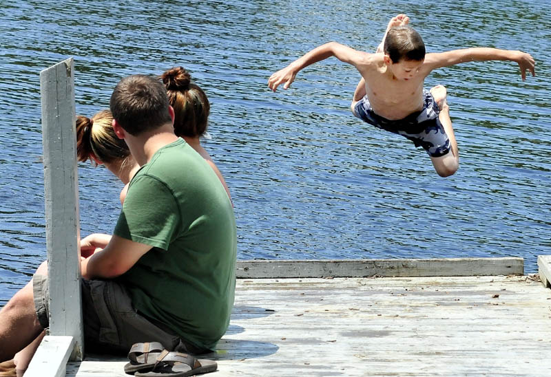 As teenagers watch, Jonathan Rogers does a backward flying leap off the dock and into the Kennebec River at the boat landing in Madison on a hot Monday.