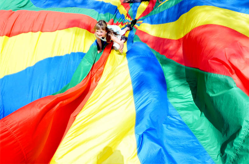 Fairfield Primary School student Kelsey Rideout tries to get to the outside of a colorful parachute as classmates flip up the sides during an end-of-school-year field day on Monday.