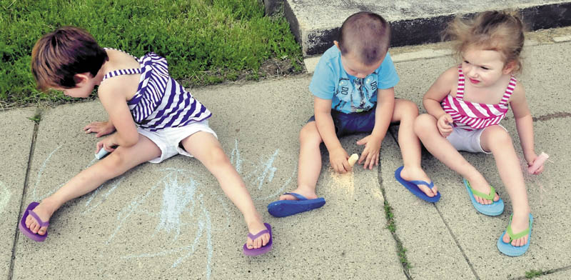 From left, Lakoda Perkins, Michael Perkins and Kailynne O'Neil added some color and shapes with chalk to a drab sidewalk in Waterville on Sunday.