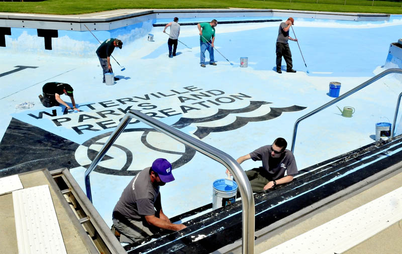 Waterville Parks and Recreation department employees including Sam Green, left, and Nate Bernier paint the large pool on North Street on Monday. The pool is scheduled to open June 22.