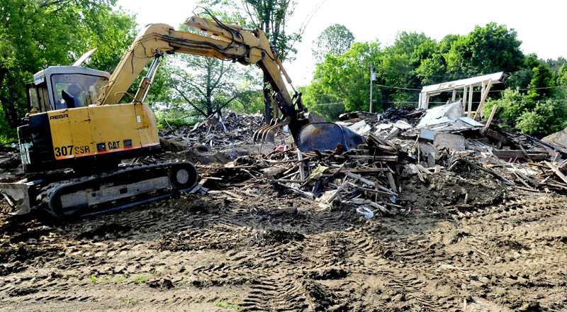 Workers this week break up the remaining sections of an apartment house on Main Street in Unity that was destroyed by fire in March. The lot will be covered with dirt and seeded until a decision is made on developing the lot, according to owner Ralph Nason Sr.