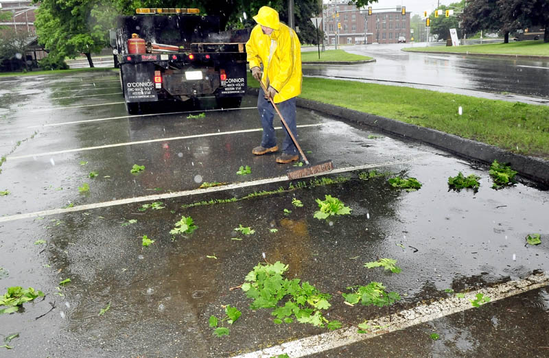 Bobbie Bellows of the Waterville public works department sweeps leaves and branches after trimming trees overhanging Front Street on a wet Tuesday.