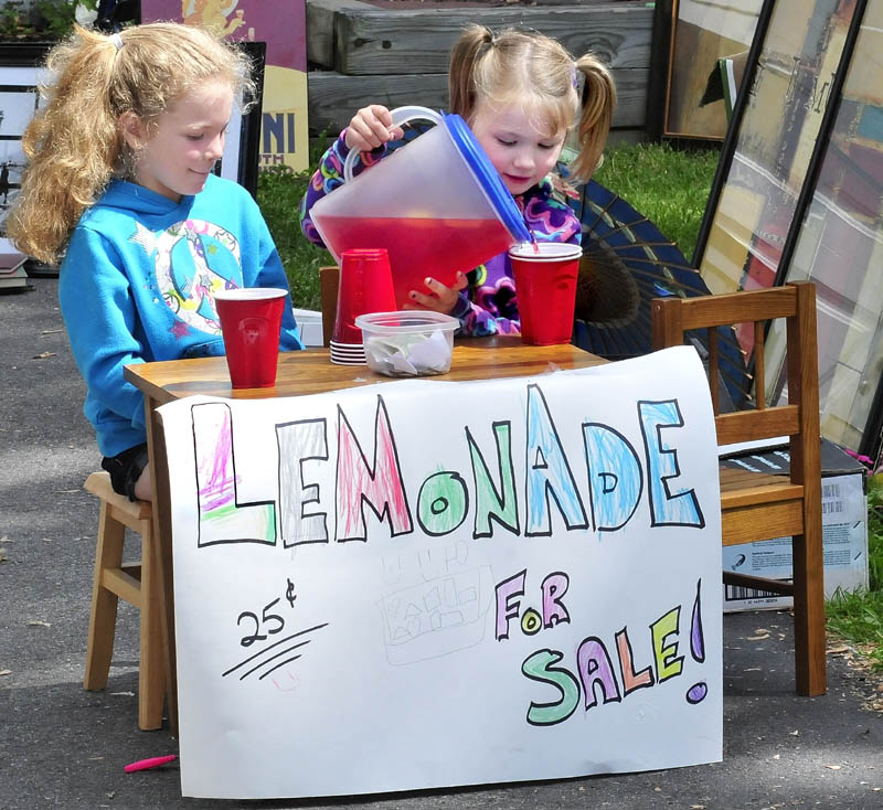 Briana Veilleux, left, and Kenadie Dickey fill cups with lemonade at their stand in Waterville on Sunday, The girls said that sales were steady enough to require a second pitcher.