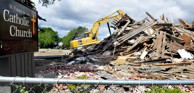 Workers with Danley Demolition have reduced the St. Francis de Sales Catholic Church in Waterville to a pile of rubble on Tuesday. The church and two other nearby buildings have been torn down to make way for a housing development.