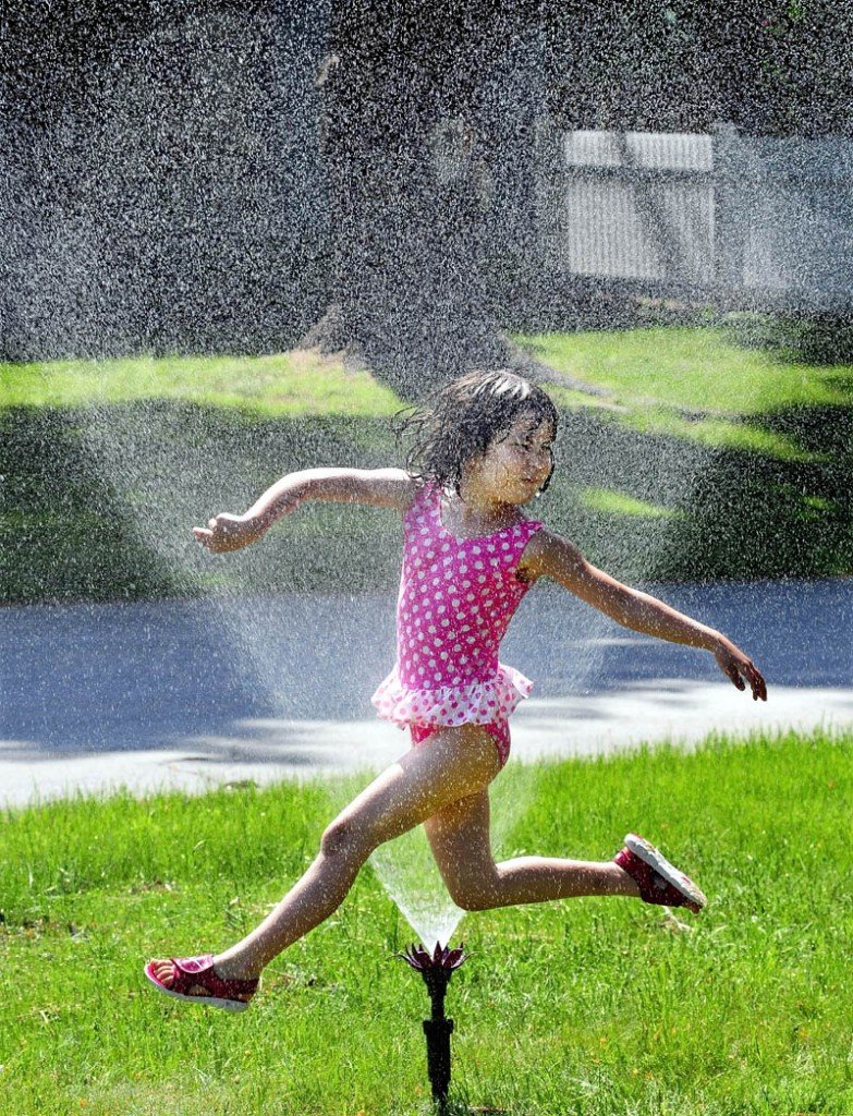 The hot weather brought out a sprinkler for Emiko Peck, seen running through the water to cool off, at her home in Waterville on a hot and muggy Sunday. Emiko and her sister, Mimako, ran from sprinkler to kiddie pool to ward of the heat.