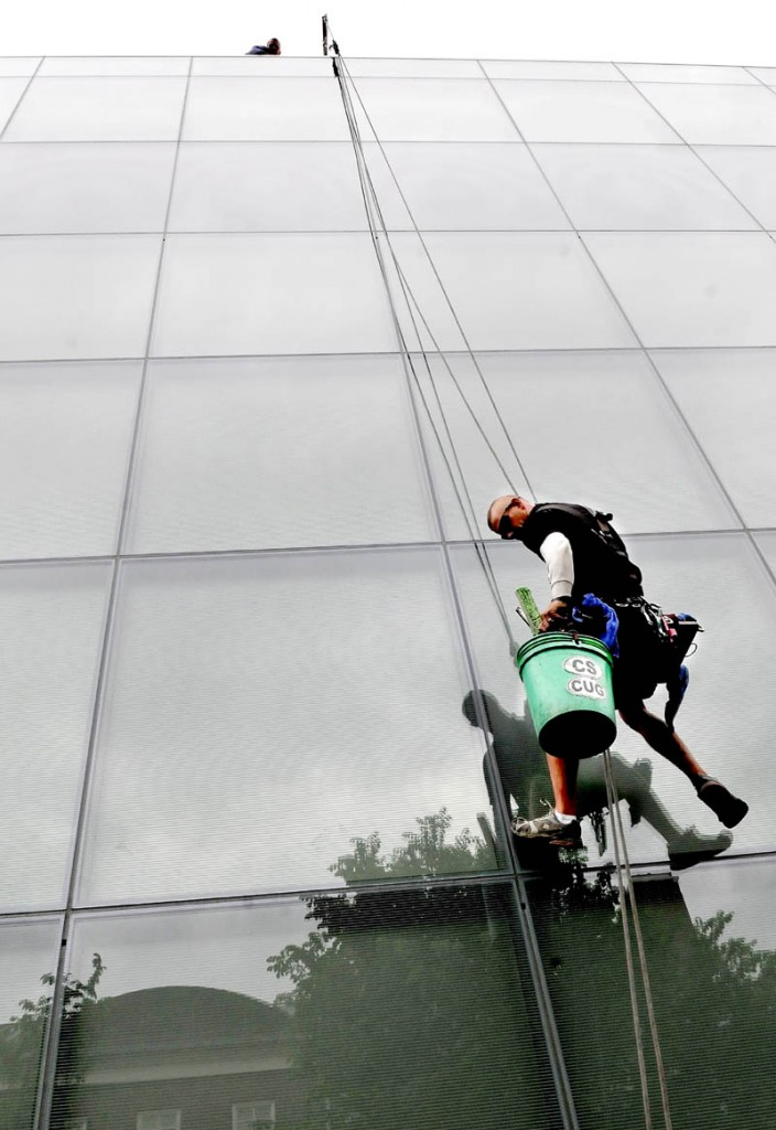Jerry Croci rappels down a huge wall of glass panes on the new Colby College Museum of Art in Waterville, while washing the glass on Monday. Sixty feet above Croci was Jay Schaible, who moved Croci's rope harness equipment sideways as needed.