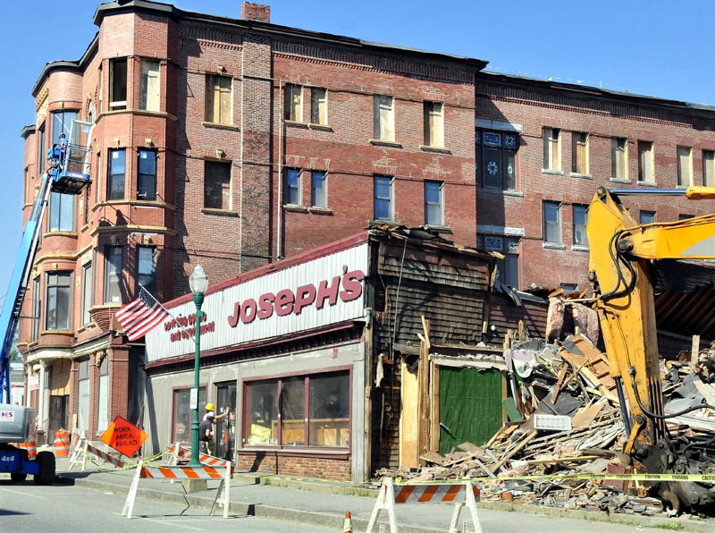 Crews tear down the former Joseph's Sporting Goods store as workers restore the Gerald Hotel on Main Street in Fairfield on Thursday.