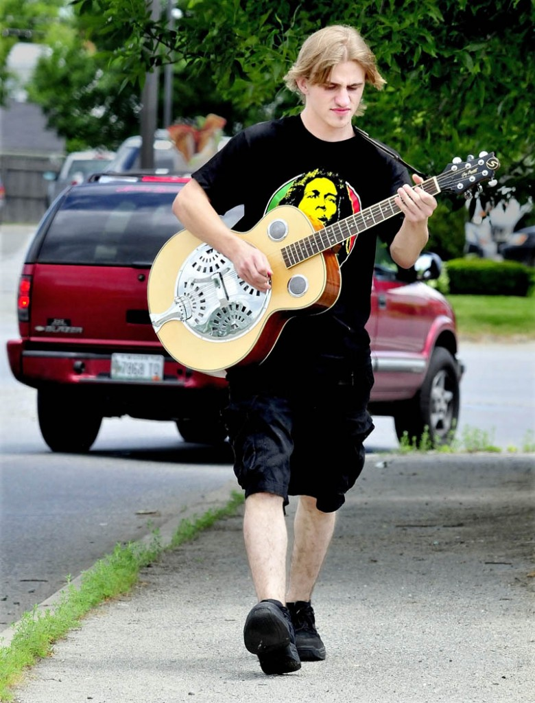 Matt Duest plays his guitar while walking to Walmart in Skowhegan on Monday.