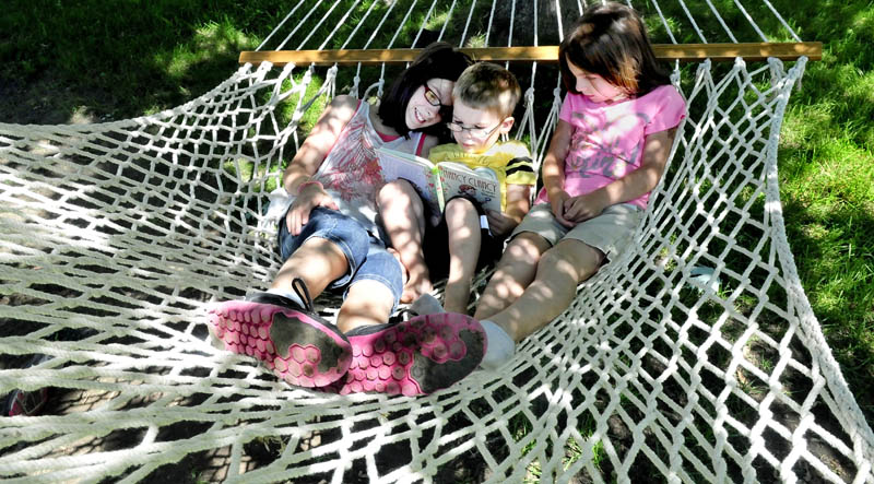 The McAlpine children beat the heat by grabbing a book and reading on a hammock in the shade at their home in Waterville on Monda. From left are Jenna, Iain and Audrey.