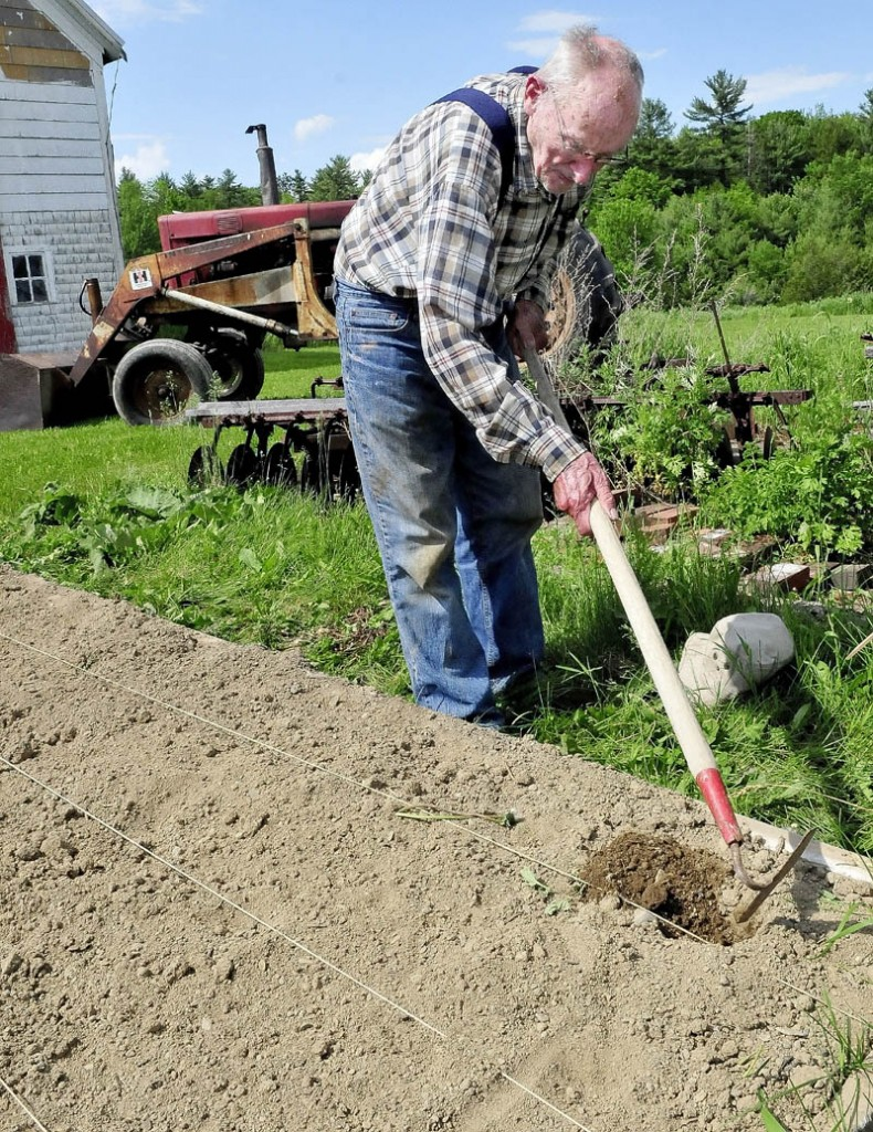Merton Webber works the soil in one of his raised garden beds at his farm in Winslow on Tuesday. Webber, 90, has gardened and farmed for most of his life, he said.