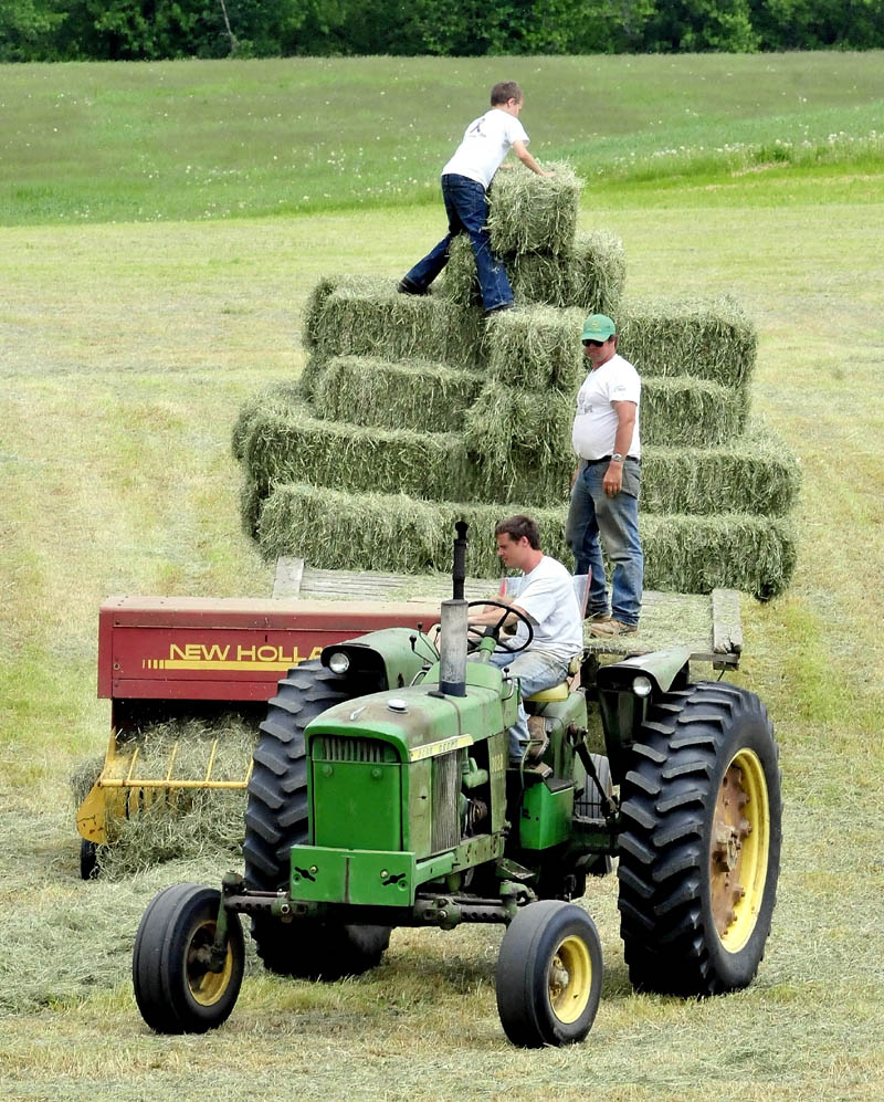 Rick Davis lll operates the tractor as his father Rick Davis ll and son Alex stack hay bales in a field at the Silver Valley farm in New Sharon on Thursday. The farmers were hurrying to beat the next two days of rain.