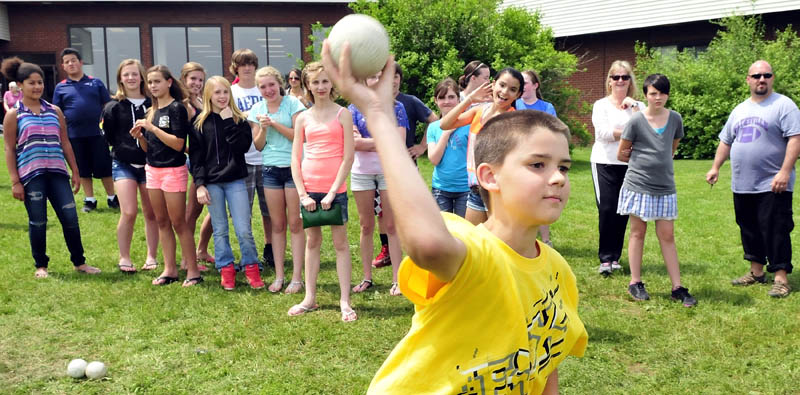 """Waterville Junior High School seventh grade student Tyler Dunn throws a ball during a dunk tank fundraiser for him on Monday. Dunn is undergoing open-heart surgery in August. Students paid to throw balls and dunk school staff. A sphagetti dinner and auction fundraiser for the Dunn family will be held June 22 at 5 p.m. at the George Mitchell School. Asked how he felt about the support from friends and teachers, Dunn said, """"It makes me feel happy."""""""