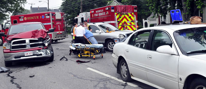 Rescue workers bring an injured man to an ambulance following an accident involving three vehicles in Waterville on Sunday. Waterville police Sgt. Dan Goss said the crash on Main Street, near Eustis Parkway, apparently was caused by driver inattention. Two people were taken to the hospital complaining of neck and back pain, but there were no serious injuries, according to Goss.