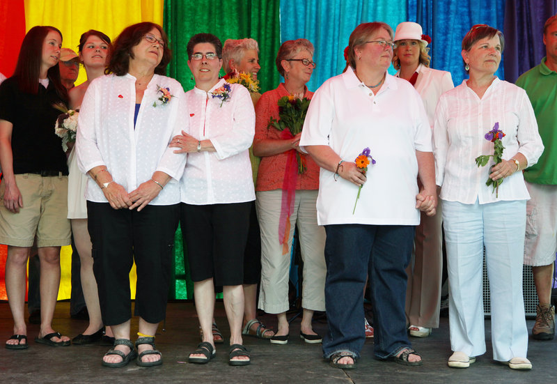 Rose Larkin, left to right, and Deb DeTuccio, joined by Chris Andre and Chris Fleuriel, right, listen to the officiant during a mass wedding Saturday at Deering Oaks in Portland as part of the 27th annual Southern Maine Gay Pride Parade and Festival.