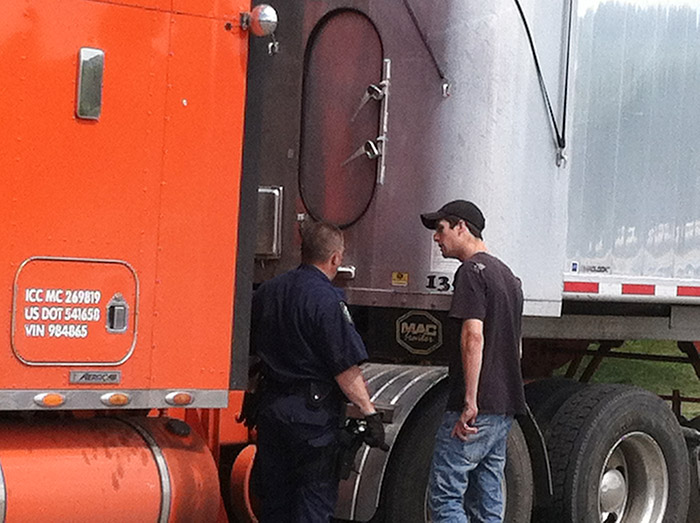 A member of the Maine State Police commercial vehicle inspection unit talks to the driver, name unknown, of the tractor-trailer police believe was involved in the fatal accident in Hanover on Friday.