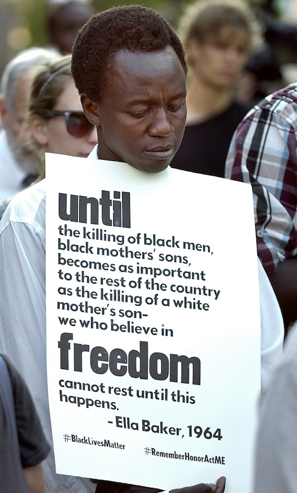 Lado Lodoka of Portland holds a sign while observing a moment of peace for Trayvon Martin at a rally in Monument Square Monday, July 22, 2013,