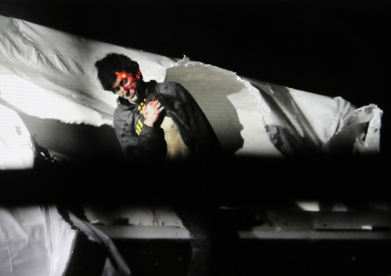 A Massachusetts State Police photo shows Boston Marathon bombing suspect Dzhokhar Tsarnaev, bloody and disheveled, with the red dot of a sniper's rifle sight on his head, emerging from a boat in Watertown, Mass.