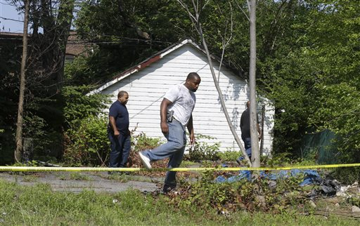 East Cleveland police search on Sunday near where three bodies were recently found, in East Cleveland, Ohio. The bodies, believed to be female, were found about 100 to 200 yards apart, and a 35-year-old man was arrested and is a suspect in all three deaths, East Cleveland Mayor Gary Norton said.