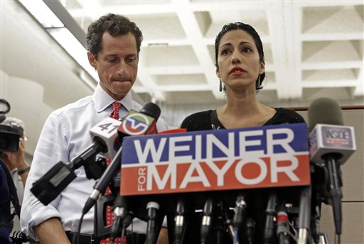 New York mayoral candidate Anthony Weiner, left, listens as his wife, Huma Abedin, speaks during a news conference at the Gay Men's Health Crisis headquarters on Tuesday in New York.