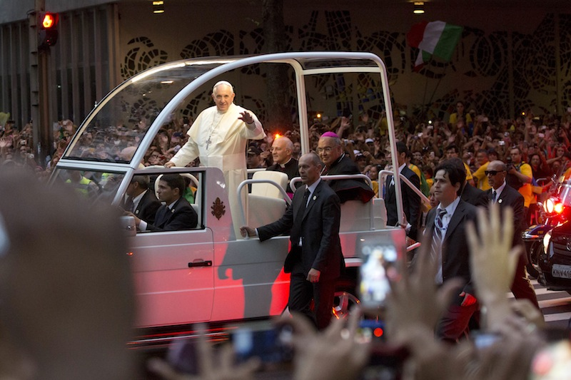 Pope Francis waves from his popemobile as he made his way into central Rio de Janeiro, Brazil, Monday. The pontiff arrived for a seven-day visit in Brazil, the world's most populous Roman Catholic nation. During his visit, Francis will meet with legions of young Roman Catholics converging on Rio for the church's World Youth Day festival.
