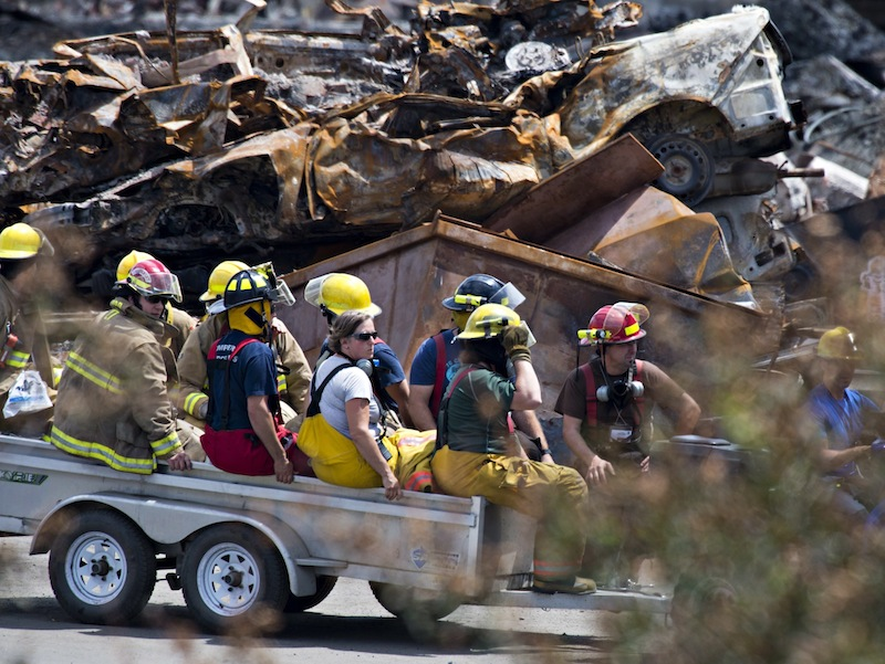 Firefighters are carried away from the train crash site in Lac-Megantic, Quebec, Sunday, July 14, 2013. Earlier this month, a locomotive and 72 tankers carrying shale oil slammed into downtown Lac-Megantic after rolling down a slope and gathering speed, killing 47 people and setting much of the downtown ablaze. (AP Photo/ The Canadian Press, Jacques Boissinot)