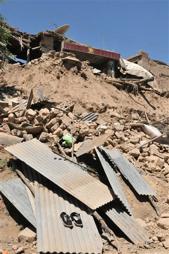 In this photo released by Xinhua News Agency, a damaged house stands in rubble following an earthquake that hit Majiagou Village of Minxian County, northwest China's Gansu Province.