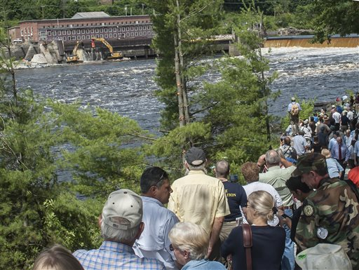 Hundreds of people watch the ceremonial breaching of the Veazie Dam from across the Penobscot River in Eddington Monday. Restoring Atlantic Salmon to the Penobscot River by the breaching of the Veazie Dam has been the collaborative effort of the Penobscot Indian Nation, seven conservation groups and state and federal agencies.