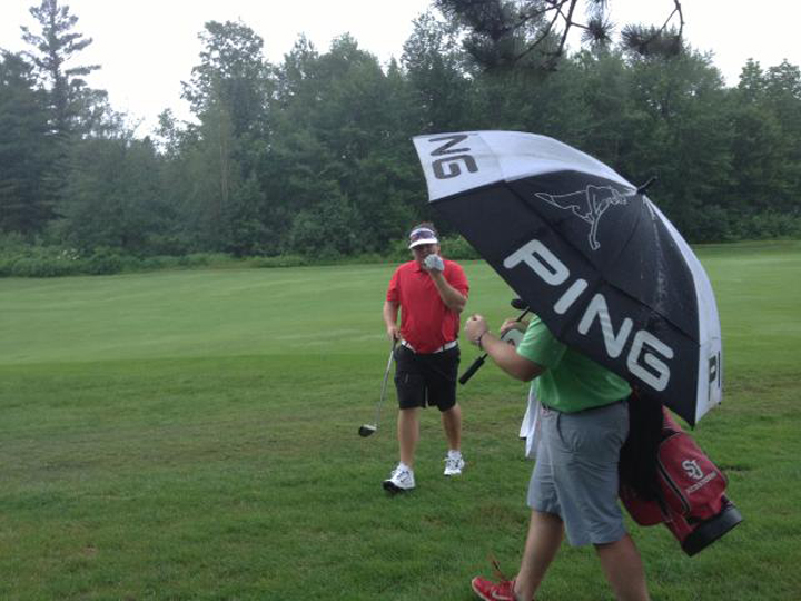Ryan Gay, left, heads for shelter under an umbrella while playing the sixth hole during a downpour today at the Maine Amateur at the Augusta Country Club in Manchester. Play was suspended at 11:55 a.m. and then resumed around 1:00 p.m. as weather cleared.