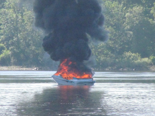 A boat burns on the Kennebec River in Pittston following an explosion on Friday.