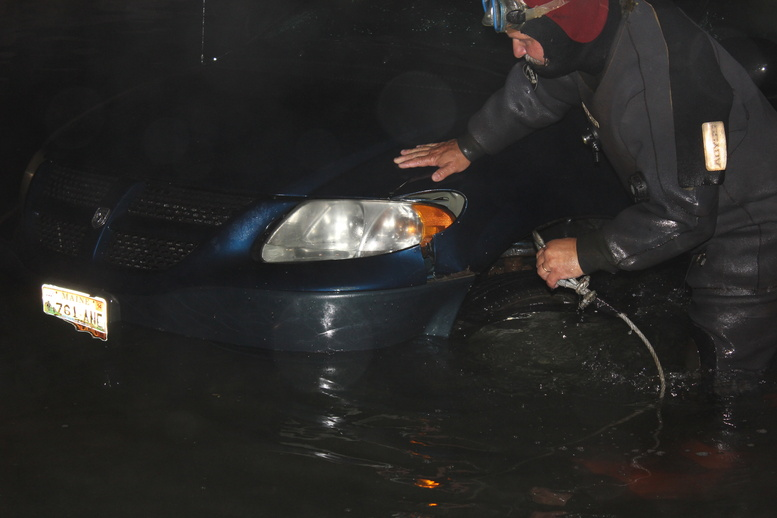 Rescue diver Travis Preston, a Jonesboro firefighter, hooks up a tow line to a minivan in the water at the scene of the double fatal accident Tuesday evening in Roque Bluffs.