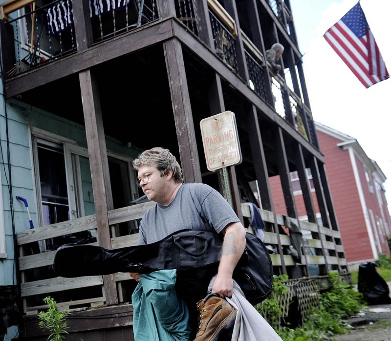 Kevin Vigue removes belongings from the apartment he's shared with his brother and uncle at 6 York St. in Augusta today, after city code enforcement, fire department and health officials ordered tenants to vacate the building because of unsafe conditions The Vigues and their uncle, Roger Nadeau, say they have lived on the second floor for about 20 years.