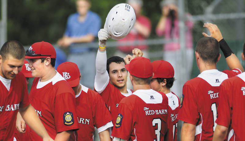 Way to go: Tayler Carrier, with helmet, is congratluated at home plate during The Red Barn's 12-4 win over Madison in the American Legion baseball Zone 2 tournament Monday in Augusta. Carrier had two home runs and a triple for The Red Barn, which won the Zone 2 title and earned a berth in the state tournament with the win.