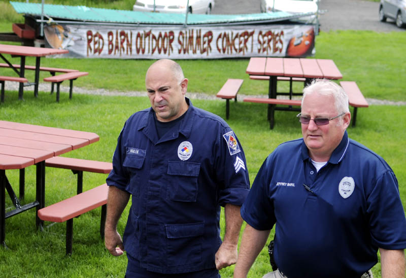 Lewiston Police officers Cpl. Jeffrey Baril, right, and Sgt. Michael Whalen walk past an outdoor stage, at top, Tuesday at The Red Barn restaurant in Augusta. Baril and Whalen stopped for lunch after attending a meeting in Augusta.