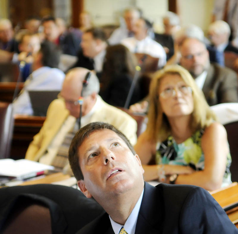 Minority Leader Rep. Ken Fredette, R-Newport, center, watches the tote board Tuesday in the House of Representatives, during consideration of overriding several vetoes issued by Gov. Paul LePage.