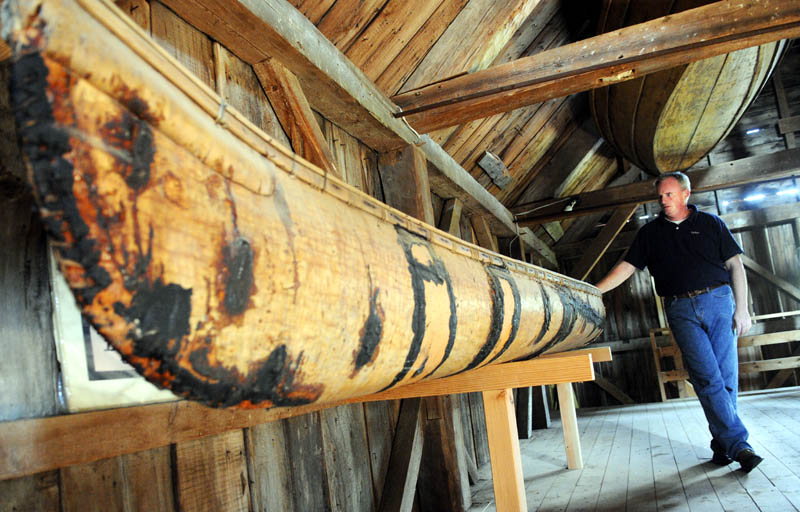 Tom Desjardin, historian with the state department of agriculture's Division of Parks and Lands, inspects a 18th Century birch bark canoe built by Native Americans, on display at the Colburn House State Historic Site in Pittston on June 25. The Kennebec Historical Society will hold a program at the house, built in 1765, on Saturday, July 13, that features a collection of boats in the barn.