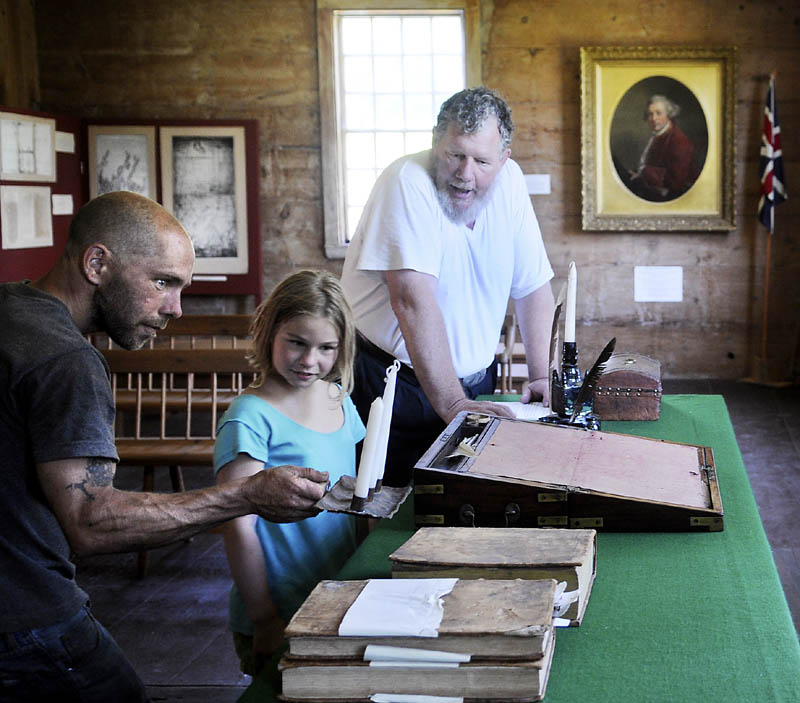Jay Robbins, right, of the Lincoln County Historical Association, gives Eric Barter, left, and his daughter, Eliza, a tour of the courtroom at the Pownalborough Court House in Dresden. The grounds of the 18th Century building that served as an inn, court and home hosted Dresden Summer Fest on Sunday.