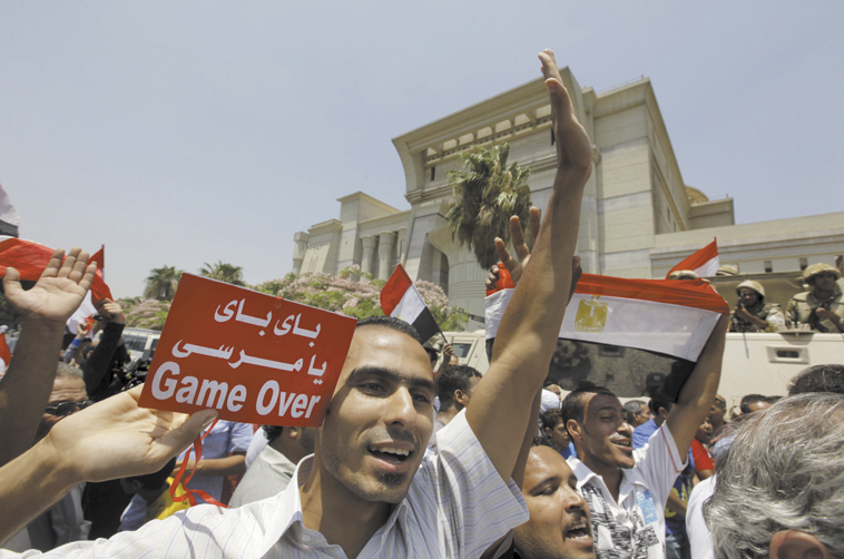 """Egyptians celebrate after Egypt's chief justice Adly Mansour is sworn in as the nation's interim president Thursday. The Arabic on the sign reads, """"bye bye Morsi."""""""
