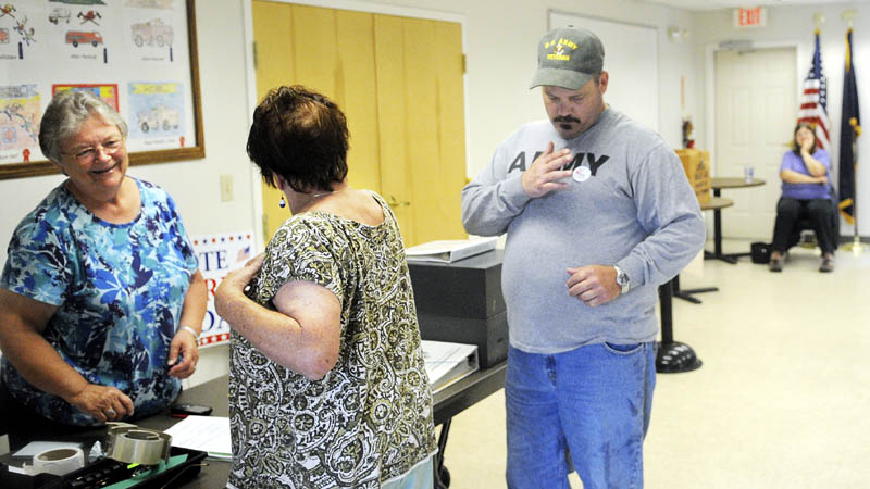 "Jefferson deputy town clerk Brenda Williams, left, confers with Cindy Hennessey as she applies an ""I Voted"" sticker, after casting a ballot today with her son, Dan, right, on the school budget. At far right is voting clerk Cheryle Fasano."