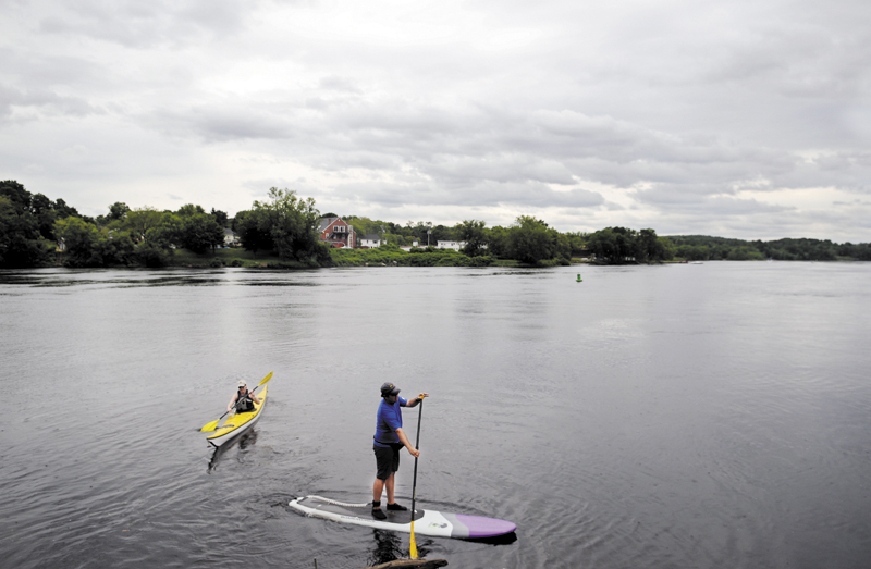 Eli Crispell, right, and Kate Browne explore the Kennebec River in Gardiner on a paddle board and kayak on Tuesday. The river furnishes several miles to explore by paddle.