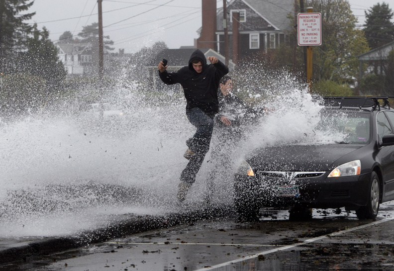 Caleb Lavoie, 17, of Dayton, Maine, front, and Curtis Huard, 16, of Arundel, Maine, leap out of the way as a large wave crashes over a seawall on the Atlantic Ocean during the early stages of Superstorm Sandy, in Kennebunk, Maine.