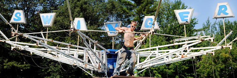 Tim Fowler rotates a ride today at the midway of the Monmouth Fair, the day before the annual agricultural exhibition opens. Gates open at 8 a.m. Wednesday and close Saturday night after the stage show. The Swinger, according to employees of midway operator Kavanaugh Amusements, is a family ride, with seats to propel people up and down while rotating in a circle at moderate speeds.