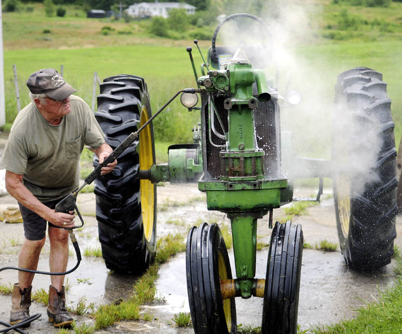 """Jim Norton steam cleans a 1955 John Deere tractor Monday he's rebuilding at his Farmingdale farm. """"Just giving her a bath,"""" Norton said of restoring the antique implement, while waiting for the hay to dry for the first cut of the season."""