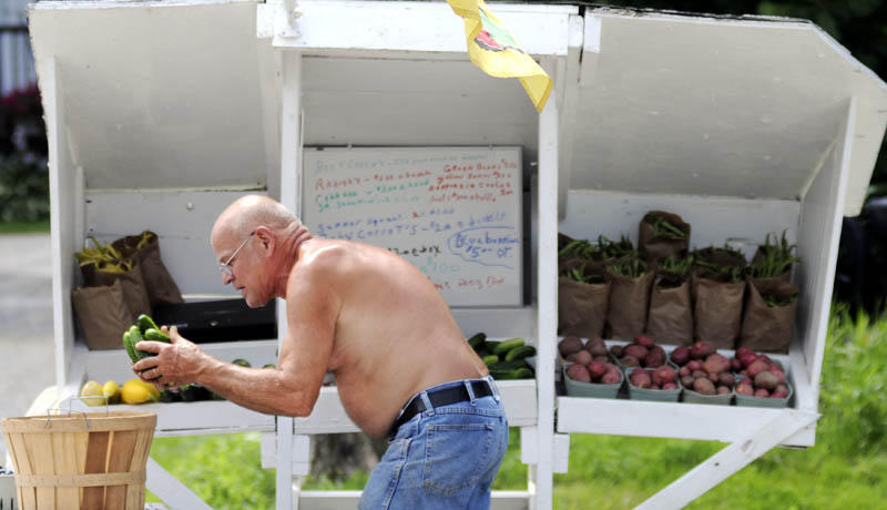 Roy Harrington stacks cucumbers that he dipped in water at the farm stand next to his family's plot in Manchester on Sunday. Harrington said he's transitioning from a semi-retired small engine mechanic to a full-time farmer, with his vegetable garden and selection of fruits.