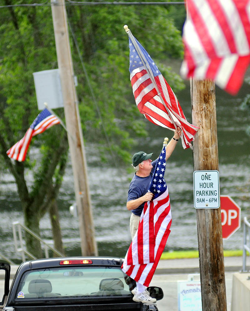 Bob Hurley replaces a flag Wednesday on Main Street in Richmond. Hurley and Tom Sullivan of American Legion Post 132 cruised through town updating the summer pennants on display ahead of Richmond Days this weekend.