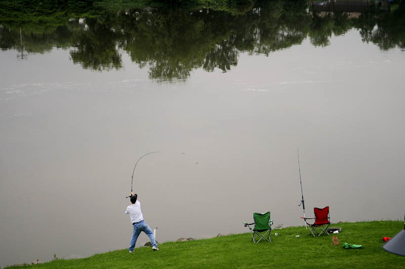 Jason Silver, of Gardiner, casts a line Monday into the Kennebec River in Gardiner. Despite high water from recent rain, several anglers fished for striped bass from the banks of the river, which was permitted beginning July 1.