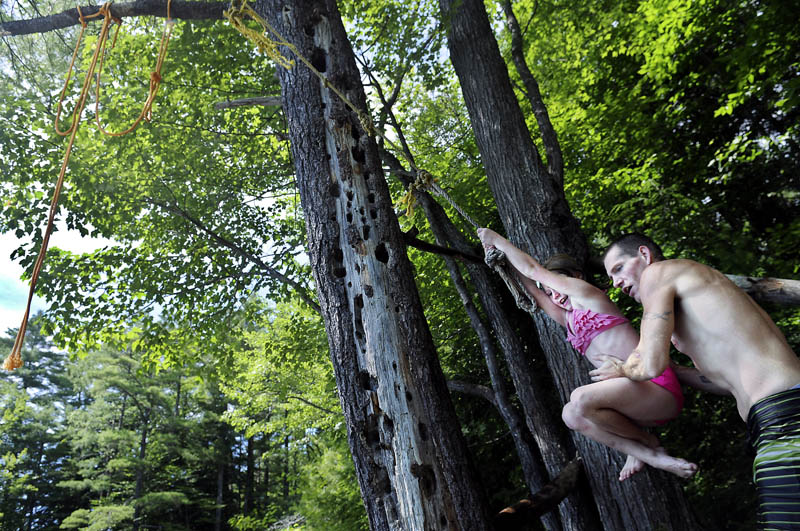 Nick Williams gives his daughter, Kiera, 7, a push on a rope swing Sunday while swimming in temperatures above 90 degrees in Augusta. The heat wave is expected to persist for the rest of the week. Williams other daughter, Lexi Merrill, 12, also took the plunge from the rope.