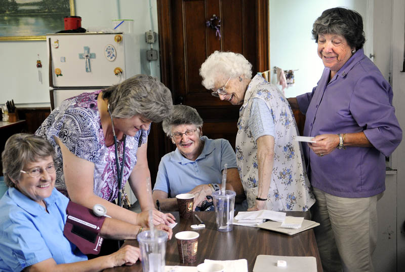 Members of the Chelsea Senior Citizens laugh Monday while comparing their blood pressure during a weekly meeting of the group on the Windsor Road. Marilyn Gagnon, left, Esther Shaw, center, Noreen Robinson and Winona Massey, right, along with other members of the group, received free checks of their blood pressure from nurse Kelley Cowing, second from left. The group meets every Monday from 11 a.m. to 2 p.m. for activities, including games, poetry readings and socializing.
